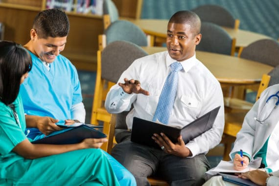 Hospital nurses, doctors, and administrators having healthcare staff meeting